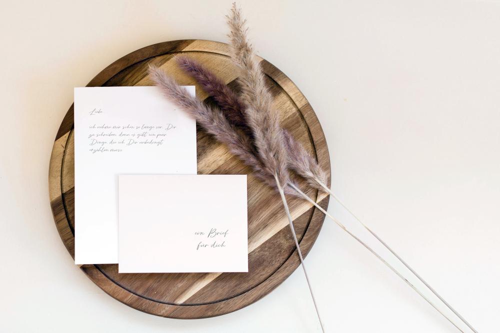 Handgeschriebener Brief mit Umschlag auf einem Holzbrett