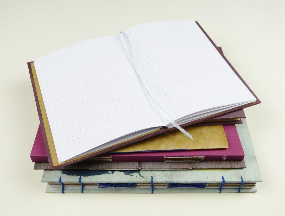 Stapel Notizbücher und aufgeschlagenes Bullet Journal für Listen
